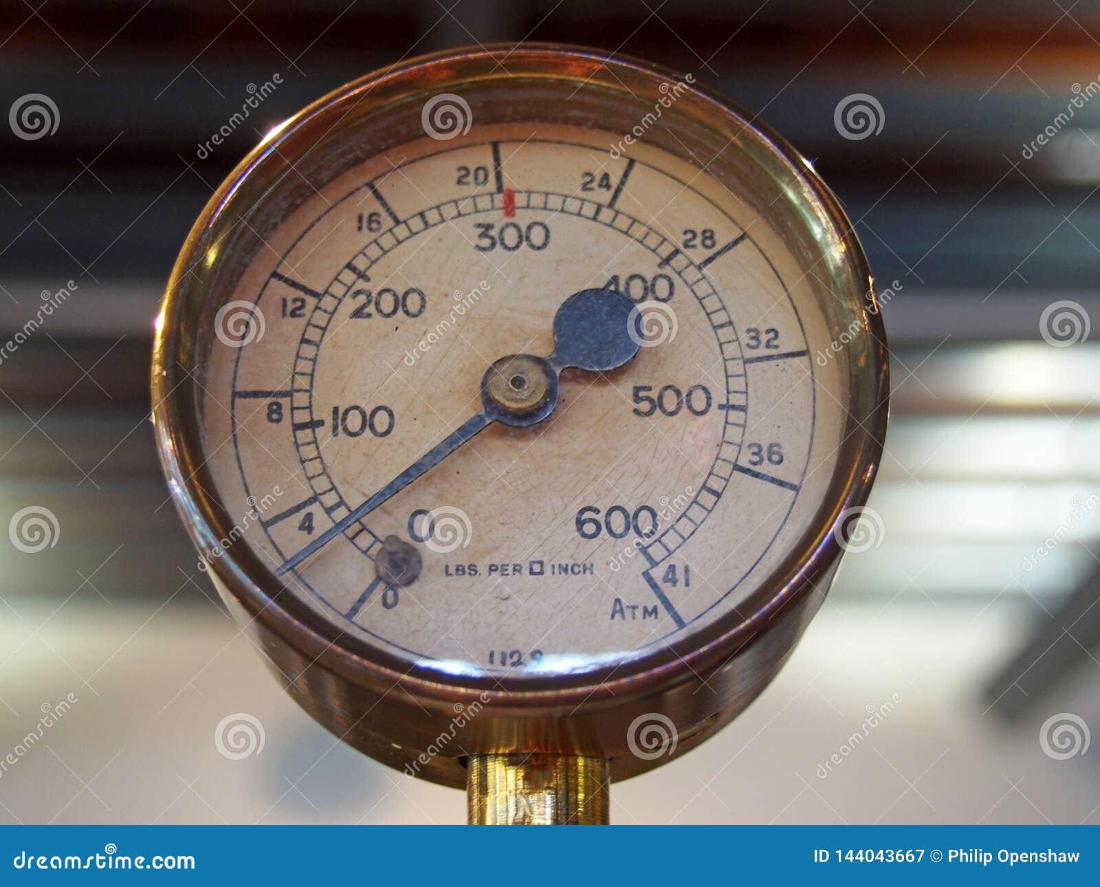 Calibre de pressão redondo de bronze brilhante velho com um seletor redondo marcado nos números e em uma agulha preta do metal