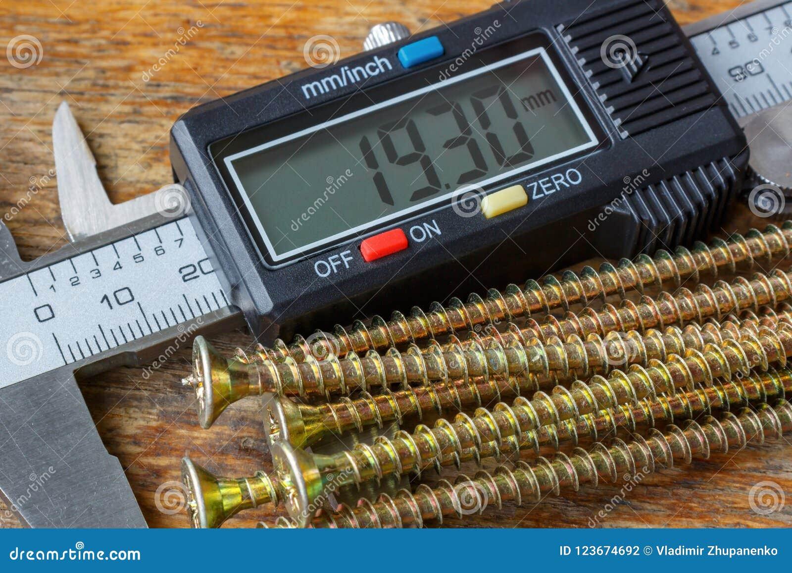 Calibro elettronico di Digital con le viti lunghe gialle sulla tavola di legno in primo piano dell officina
