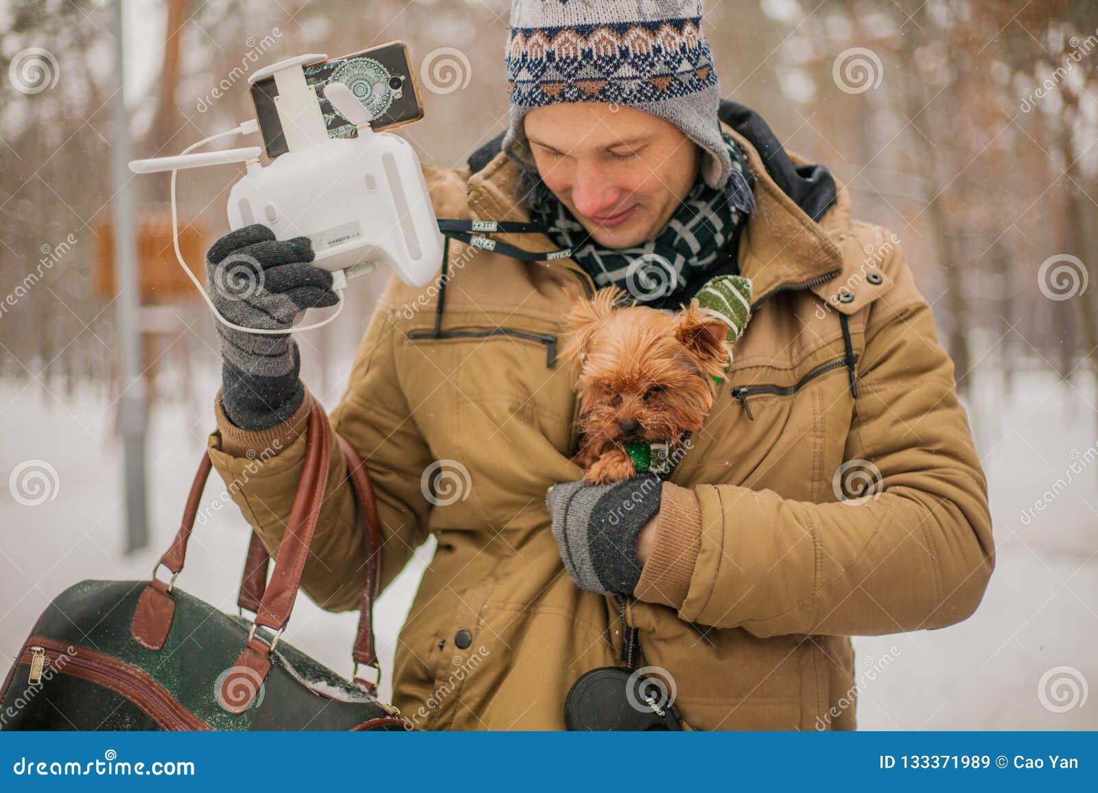 Caliente el perro debajo de la chaqueta en el invierno en la nieve cuidado para un perro en la estación fría