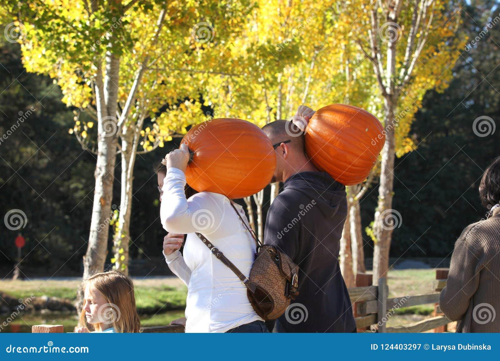 California США Октябрь 2012 Молодая семья с тыквами на их плечах идет отпраздновать хеллоуин
