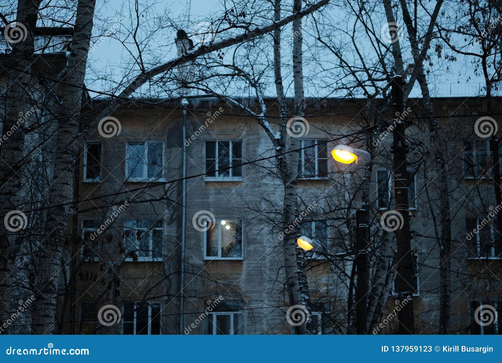 Calle cobbled estrecha en ciudad medieval vieja con las casas iluminadas por las lámparas de calle del vintage Tiro de la noche