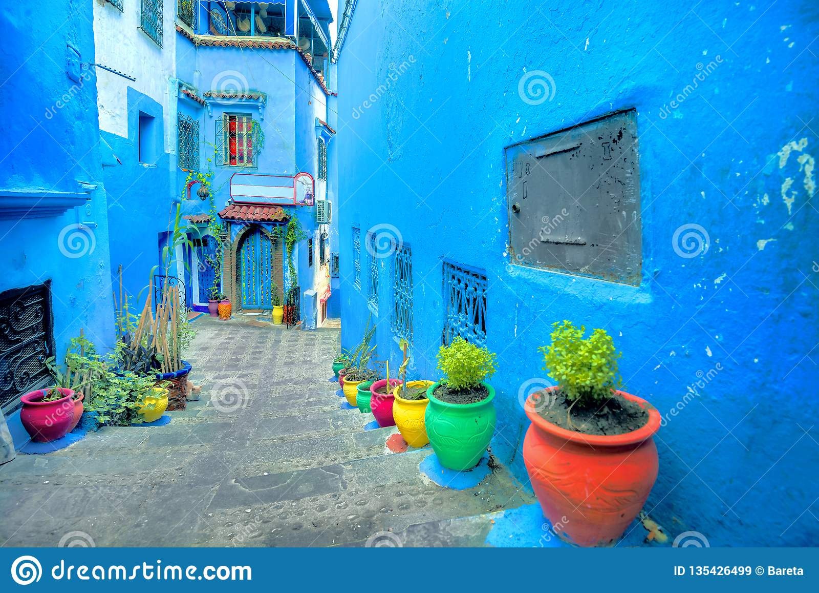 Calle con las paredes pintadas azules y las macetas coloridas en Medina viejo de Chefchaouen También ha sido sabido por su nombre