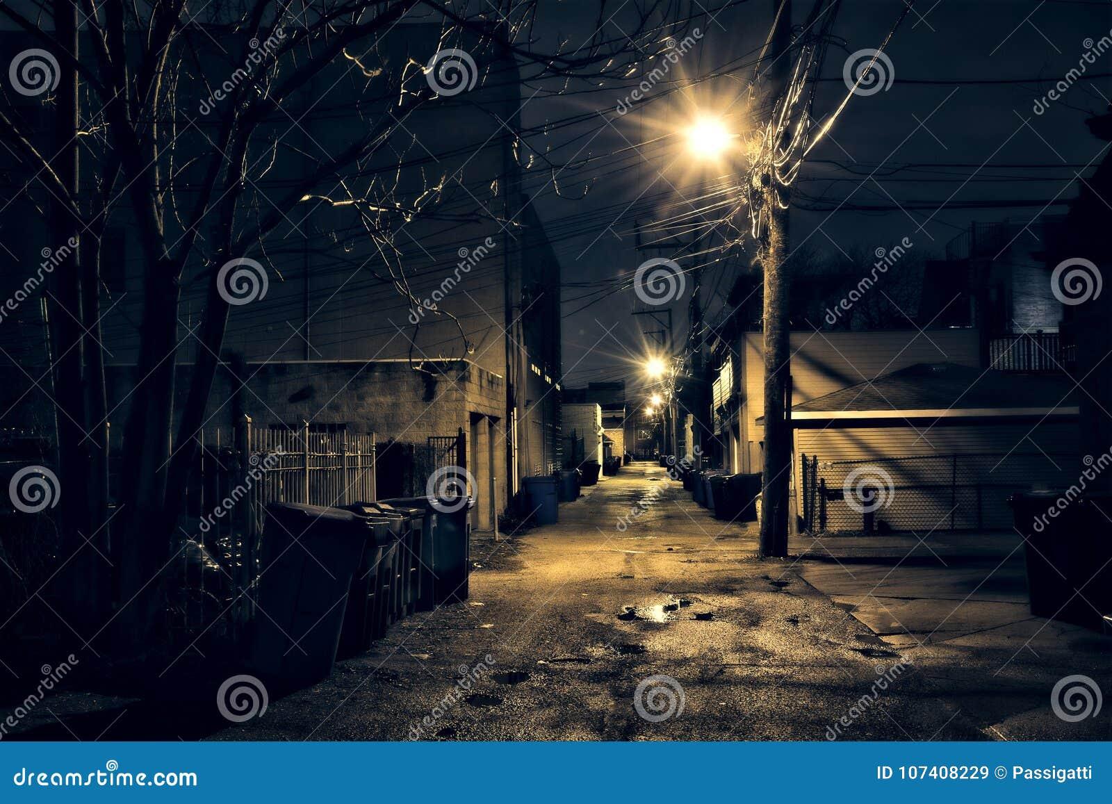 Callejón oscuro, arenoso y mojado de Chicago en la noche después de la lluvia