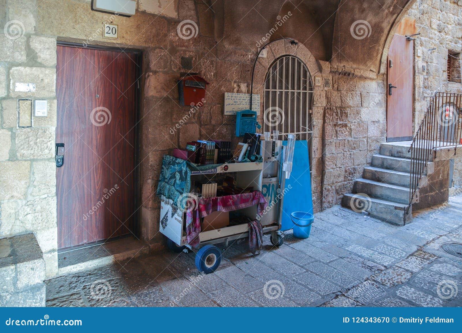 Calles silenciosas de Jerusalén Un carro con los soportes de libros religiosos en el cuarto judío cerca de una pared en la ciudad