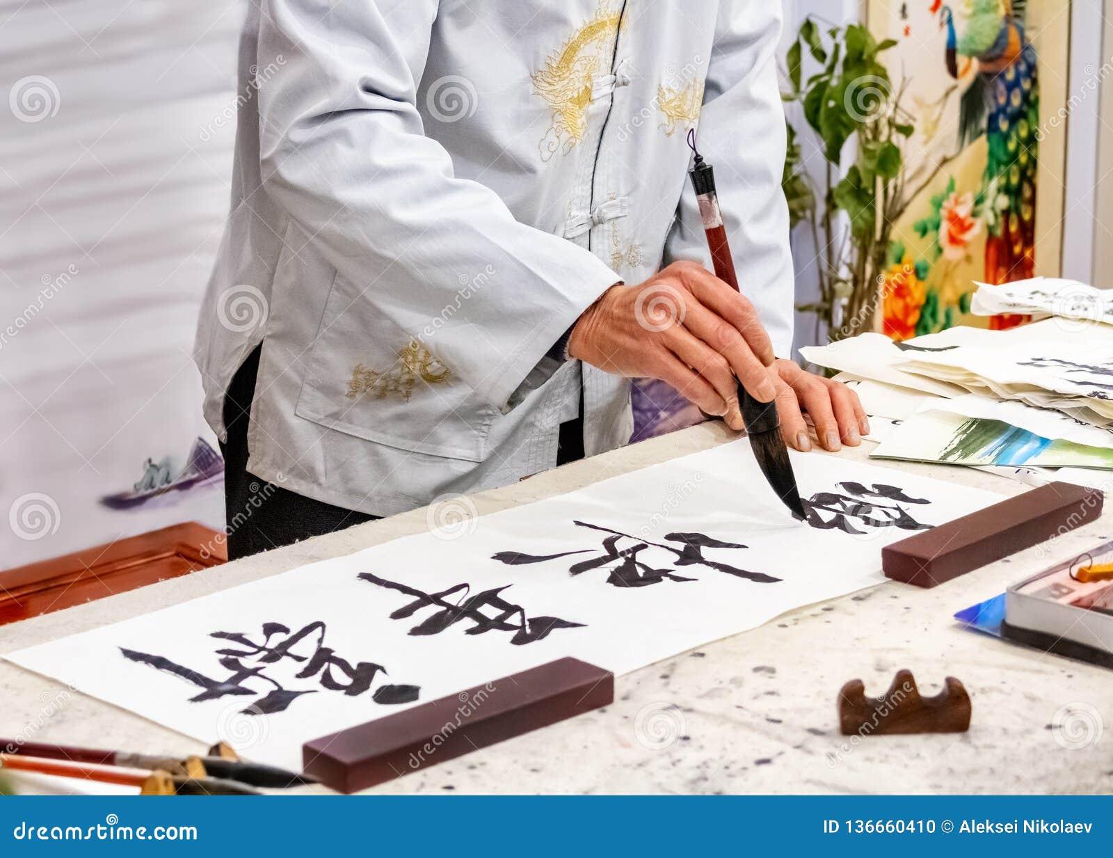 Calligraphie asiatique Le maître de la calligraphie chinoise écrit sur les caractères de papier et les hiéroglyphes de riz qui li