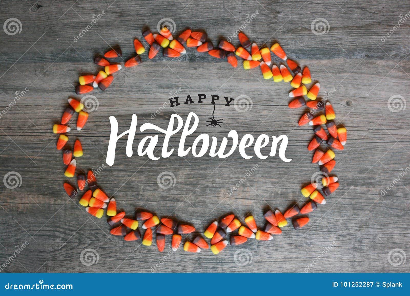 Calligraphie heureuse de Halloween avec la frontière ovale de bonbons au maïs au-dessus du fond en bois rustique, horizontal