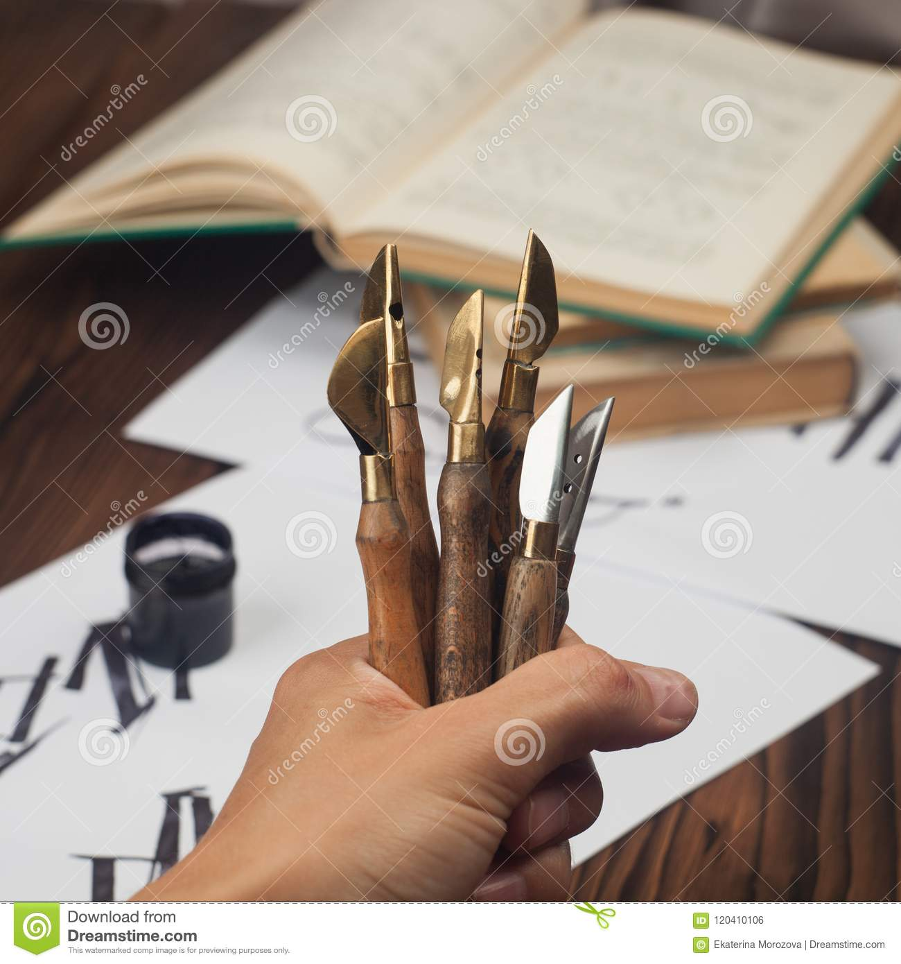 Calligraphy handwriting accessories, style fountain pens nib collection in hand, abstract paper and wooden background. Toned Photo