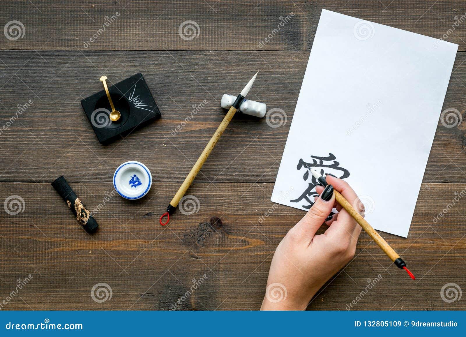 Calligraphy La mano scrive l amore del geroglifico su Libro Bianco sulla vista superiore del fondo di legno scuro