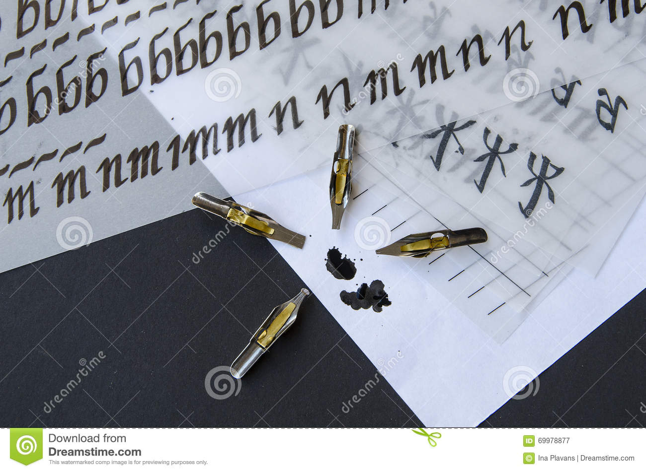 Calligraphy pen tips flat tipped nib ink and practice sheets on