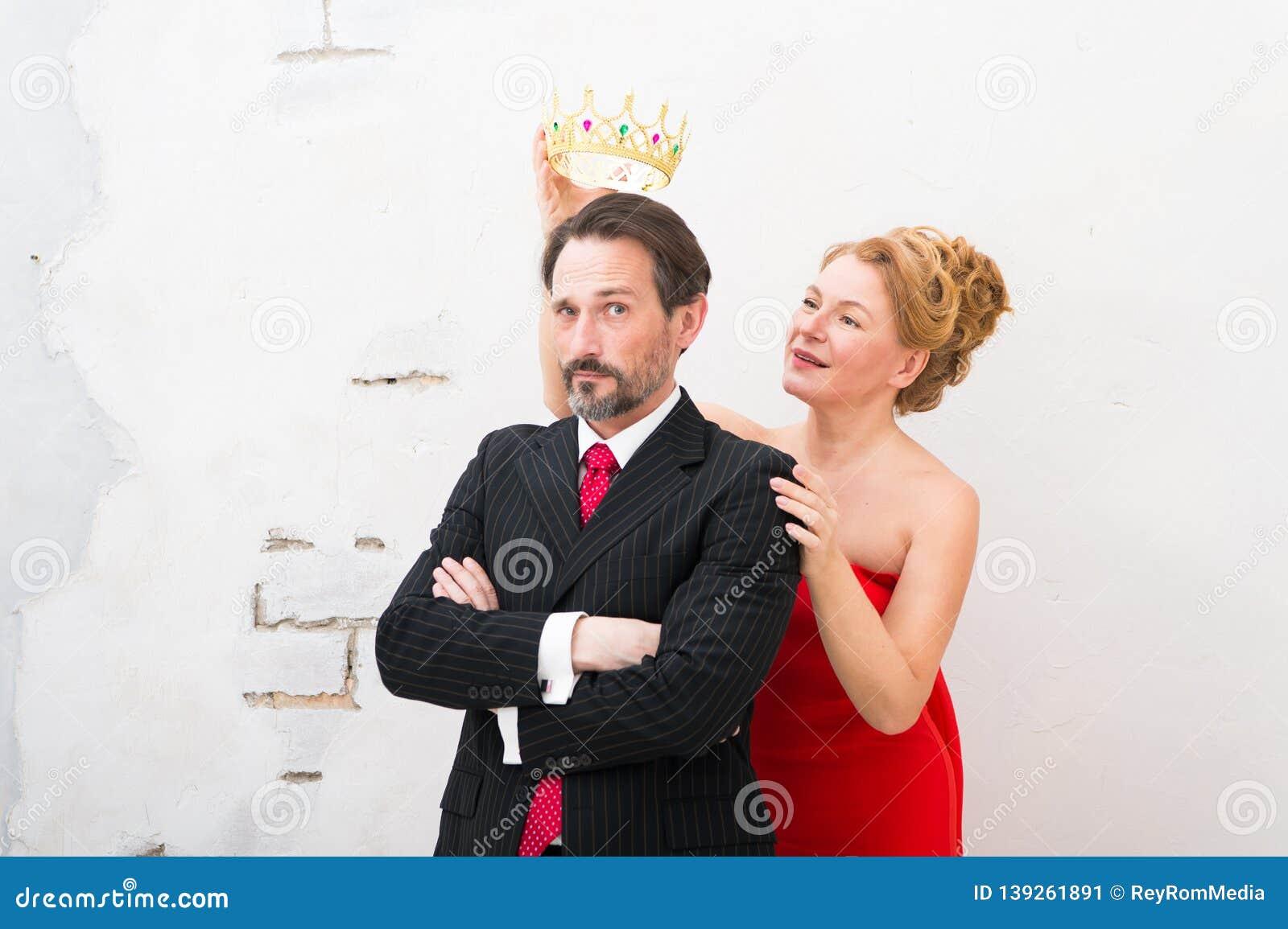 Waist up of elegant woman holding golden crown above her mans head
