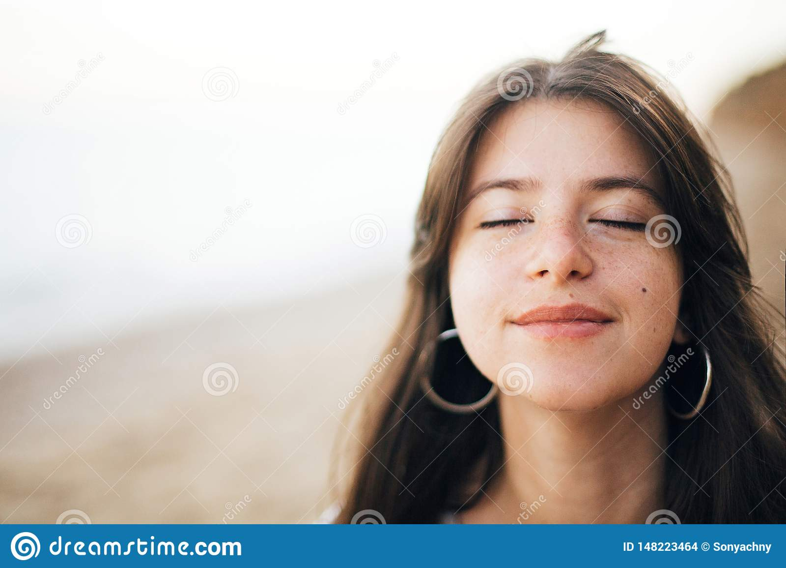 Calm portrait of happy fashionable boho woman relaxing at sandy cliff on tropical island. Stylish hipster girl walking on beach at