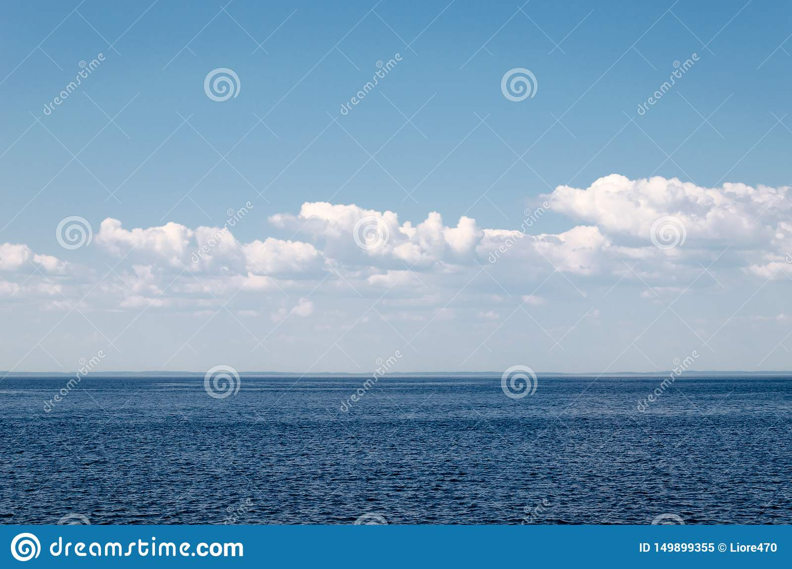 Calm sea on a background of blue sky with cloudsCalm sea against blue sky with clouds. Harmony of sea elements. Seascape. Copy