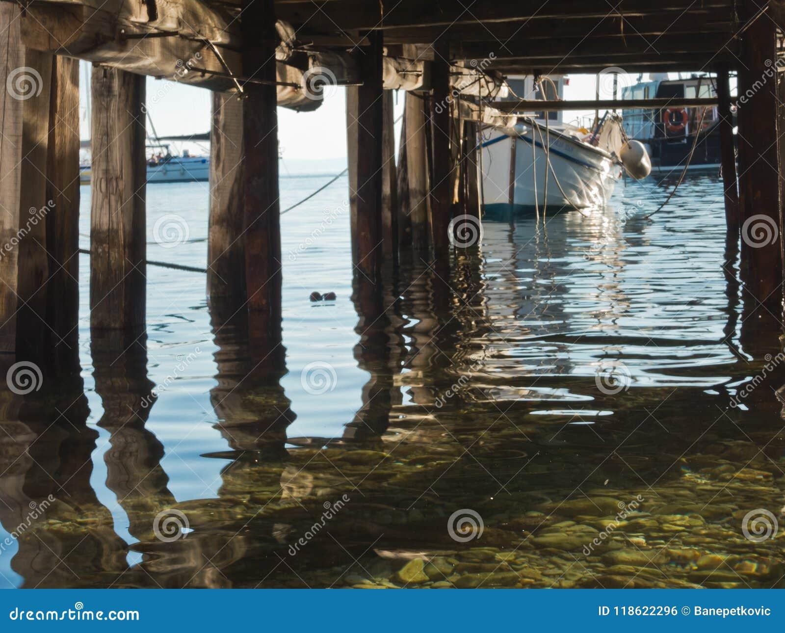 Calm sea water below old wooden pier at Agnontas beach, Skopelos island