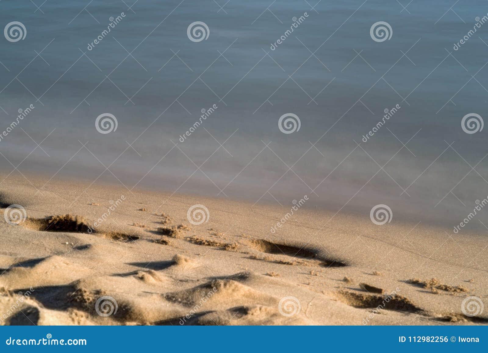 Calm waves on the sand coast