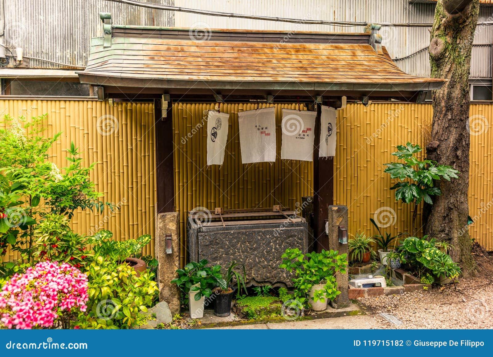 Calma na bacia da água na entrada de um santuário em Japa
