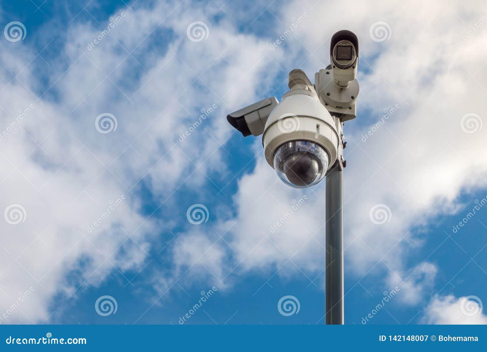 Caméras de sécurité de télévision en circuit fermé sur le poteau sur le ciel bleu avec le fond blanc de nuages