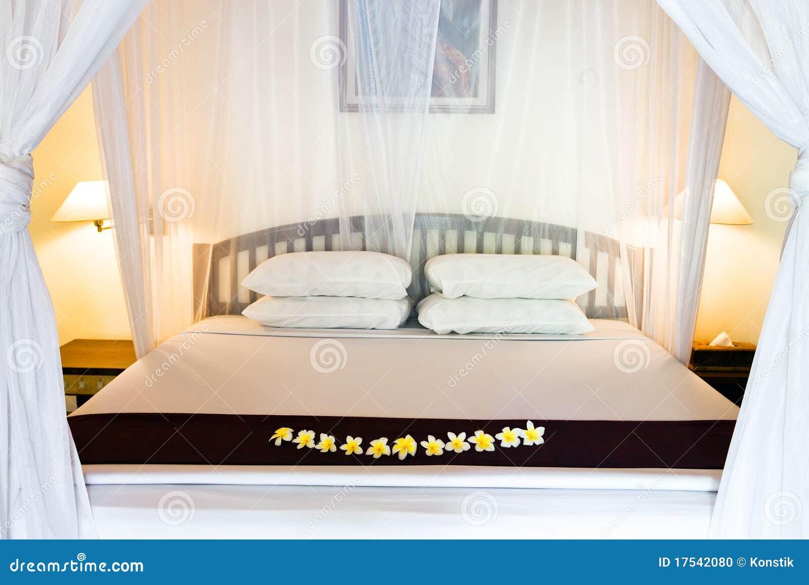 Cama ancha bajo las cortinas de la cama foto de archivo - Cortinas para cama ...