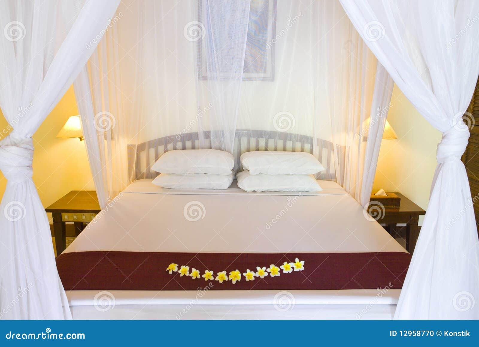 Cama bajo las cortinas de la cama foto de archivo imagen - Cortinas para cama ...