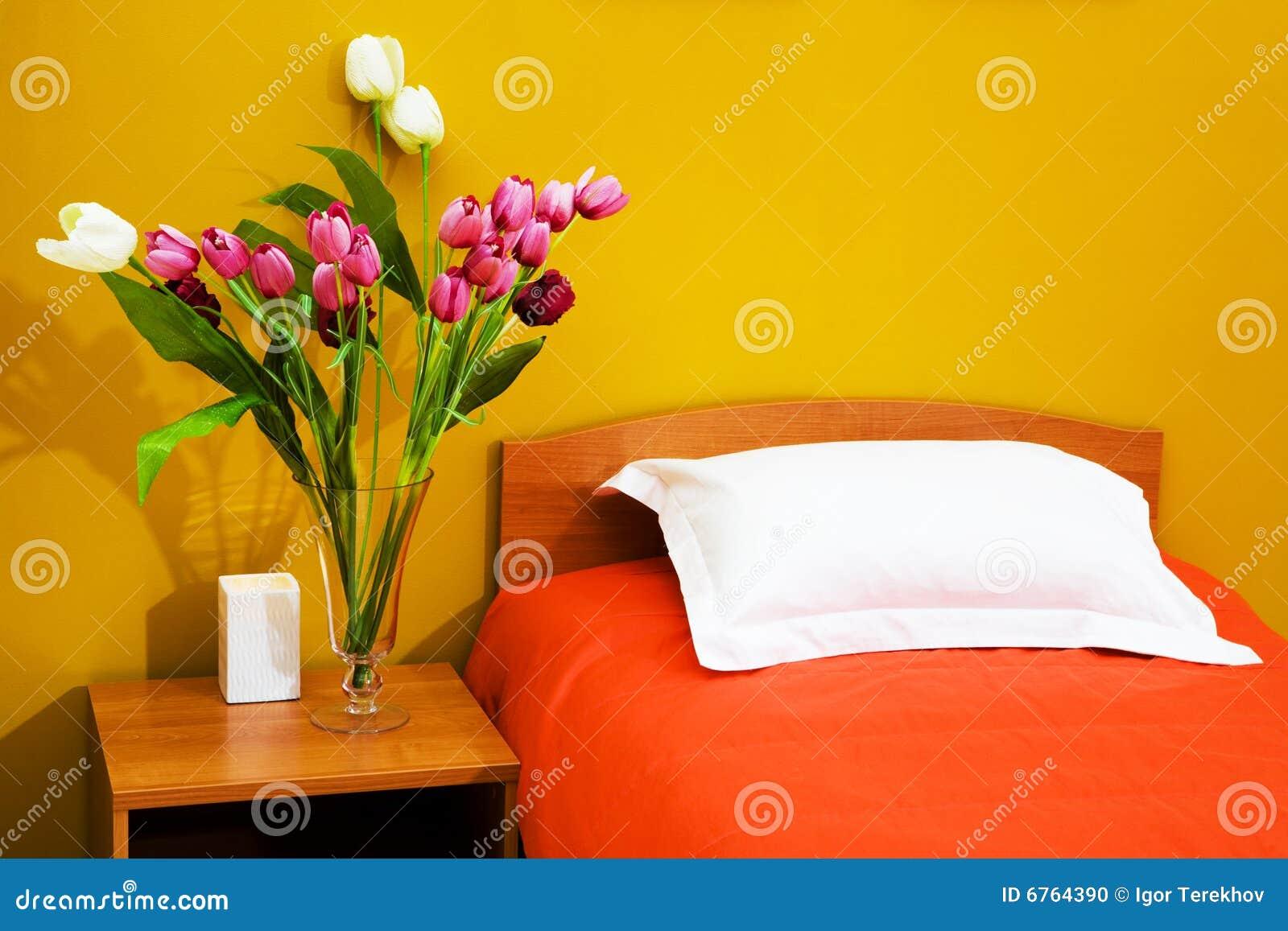 Cama con un coverlet anaranjado