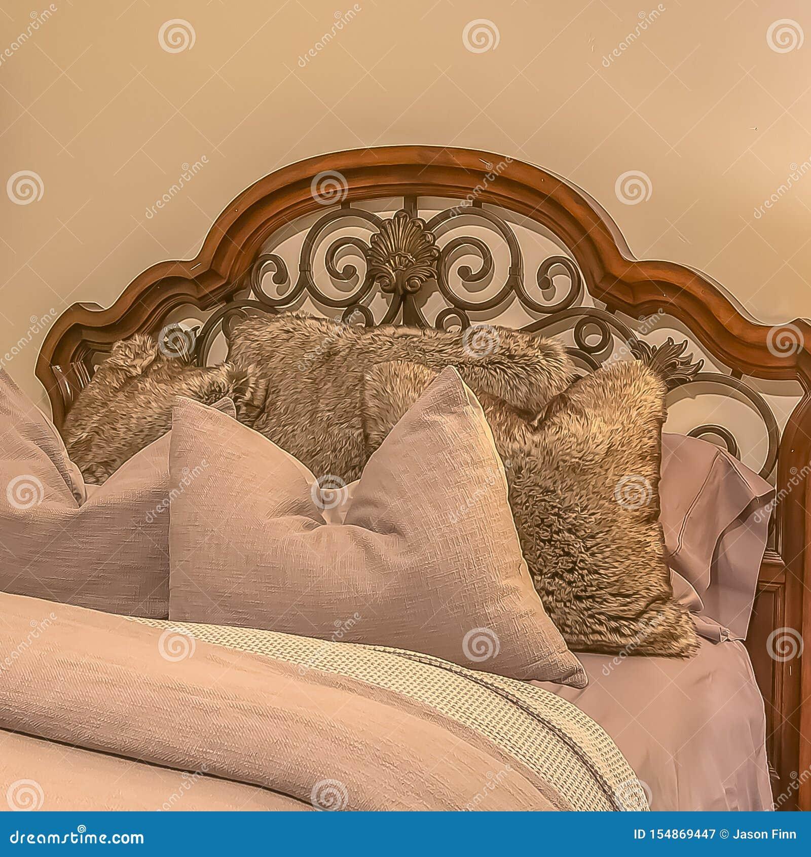 Cama cuadrada con las almohadas mullidas contra el cabecero de madera y del hierro del worught