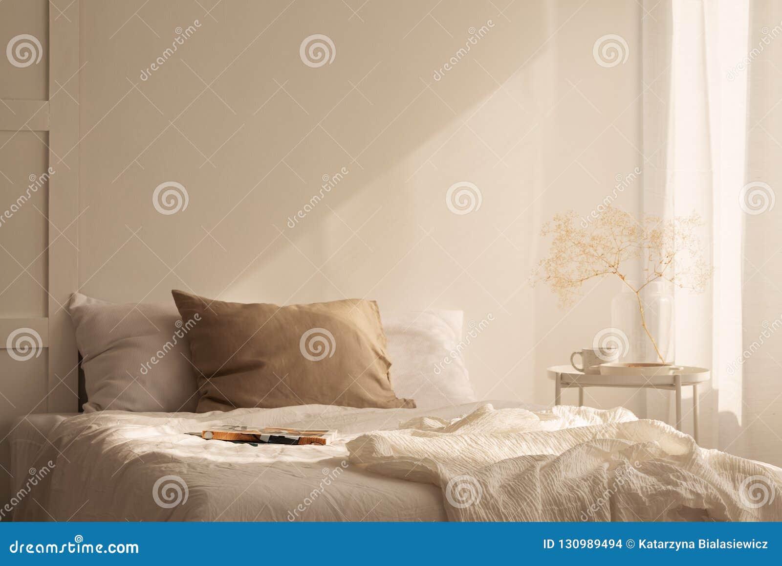 Cama gigante del ion de lino de las hojas en dormitorio mínimo con la pared vacía