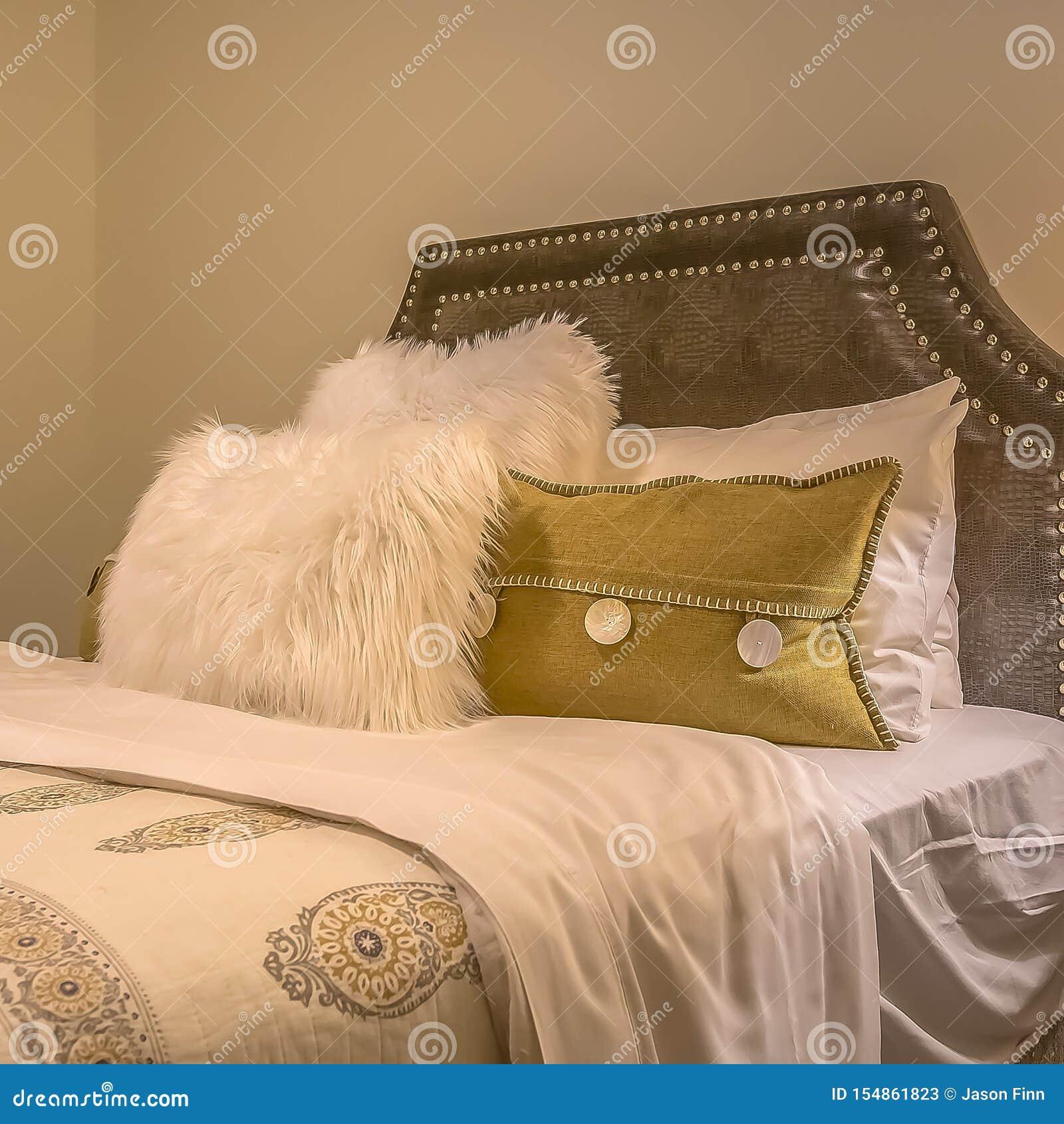 Cama matrimonial del marco cuadrado con las almohadas mullidas contra el cabecero tapizado del belgrave