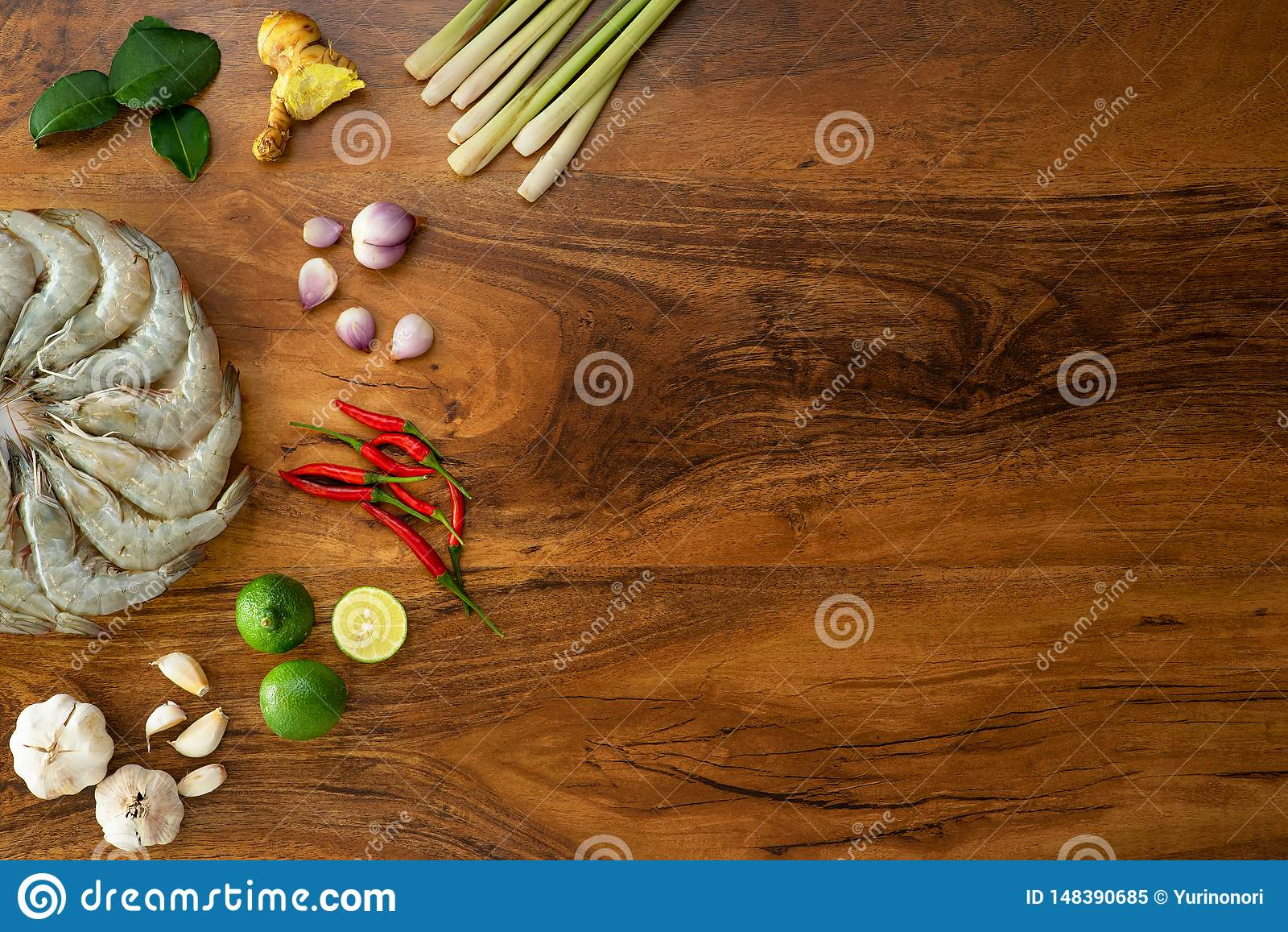 Camar?n crudo fresco en un plato blanco e ingredientes el cocinar para tom yum en el fondo de madera, visi?n superior