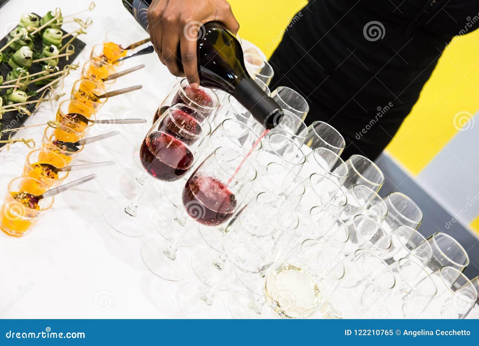Camarera Pouring Red Wine en vidrios en la tabla de comida fría con blanco