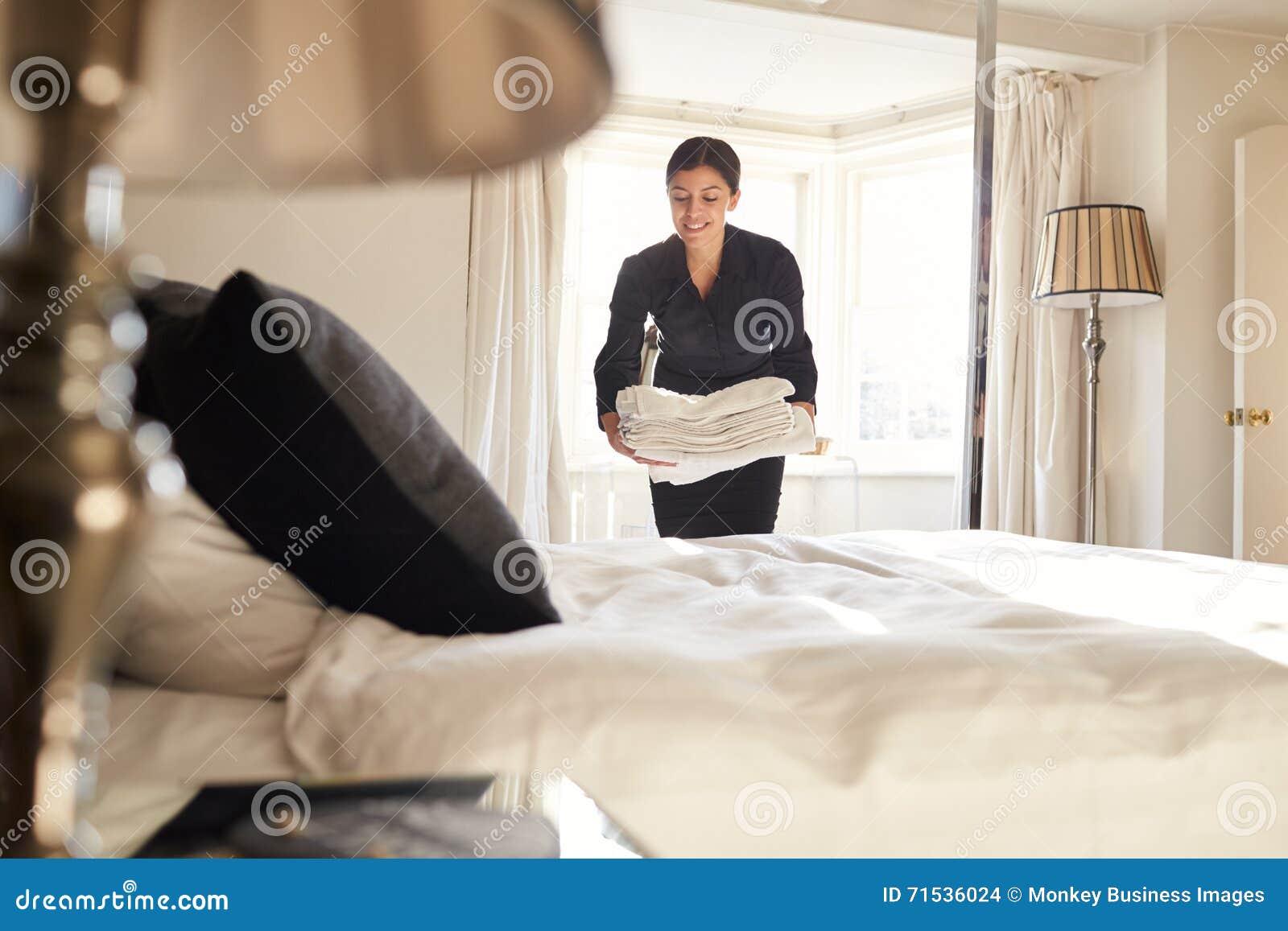 Camarera que coloca el lino en la cama de la habitación, opinión de ángulo bajo