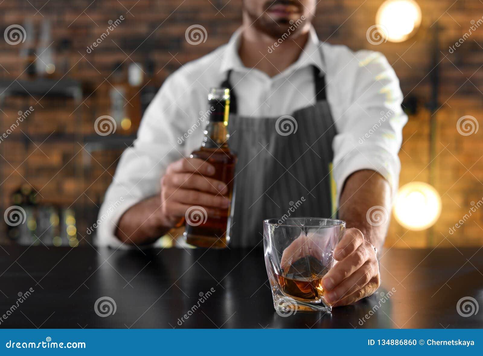 Camarero con el vidrio y la botella de whisky en el contador en la barra, primer