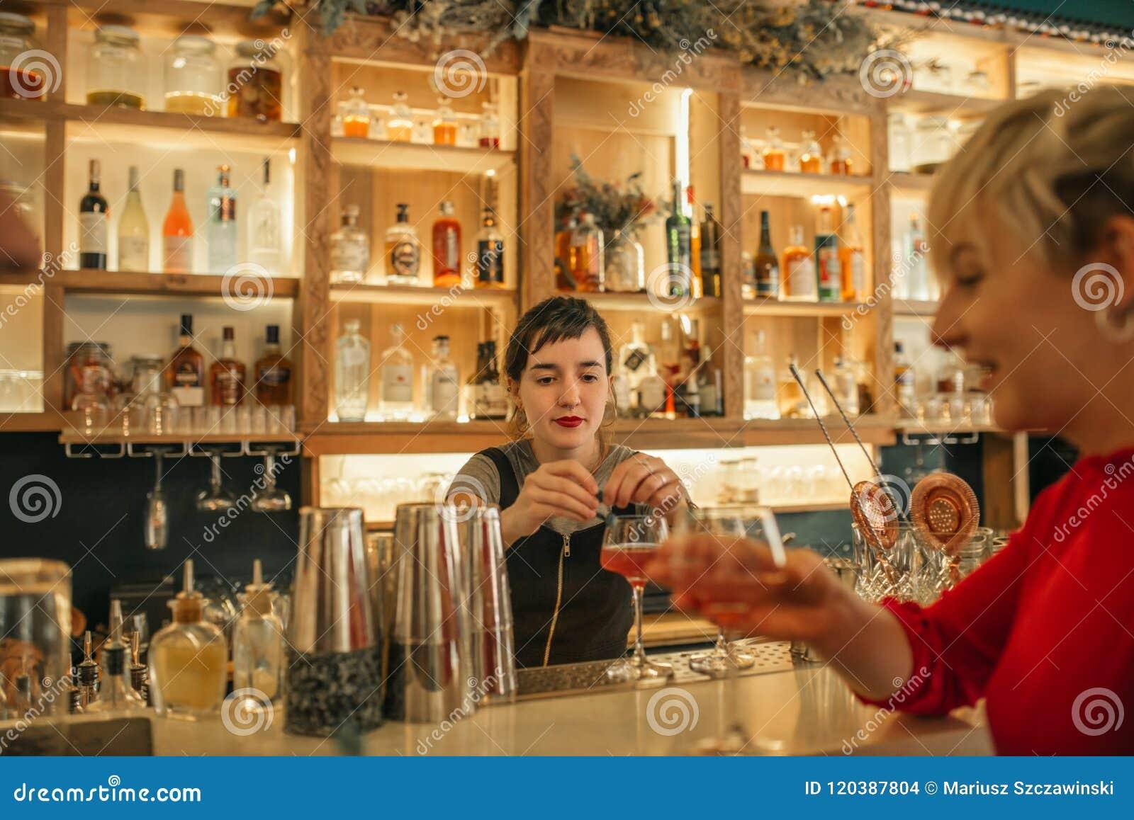 Camarero de sexo femenino joven que hace los cócteles detrás de un contador de la barra