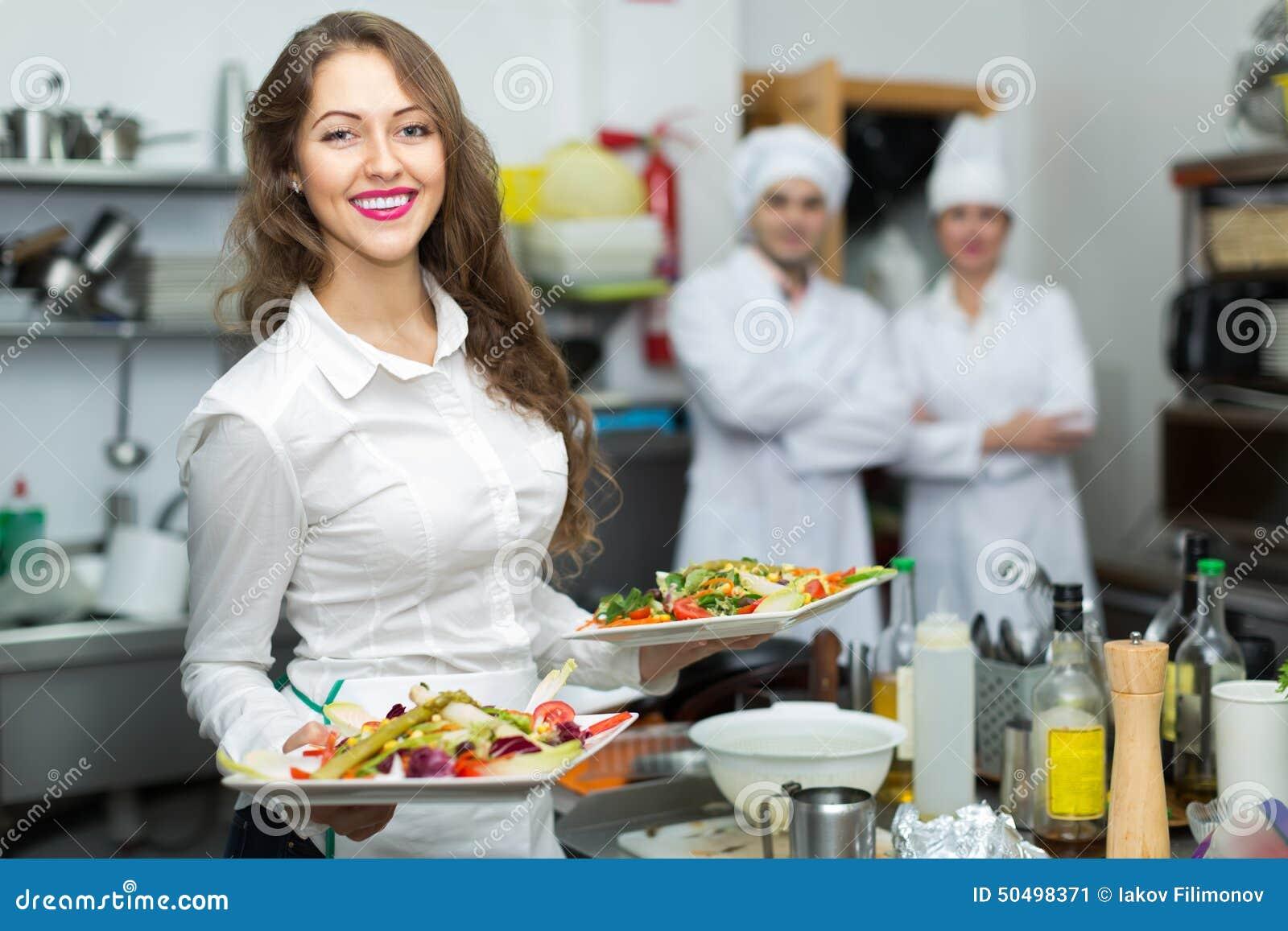 Camarero de sexo femenino que toma el plato en la cocina
