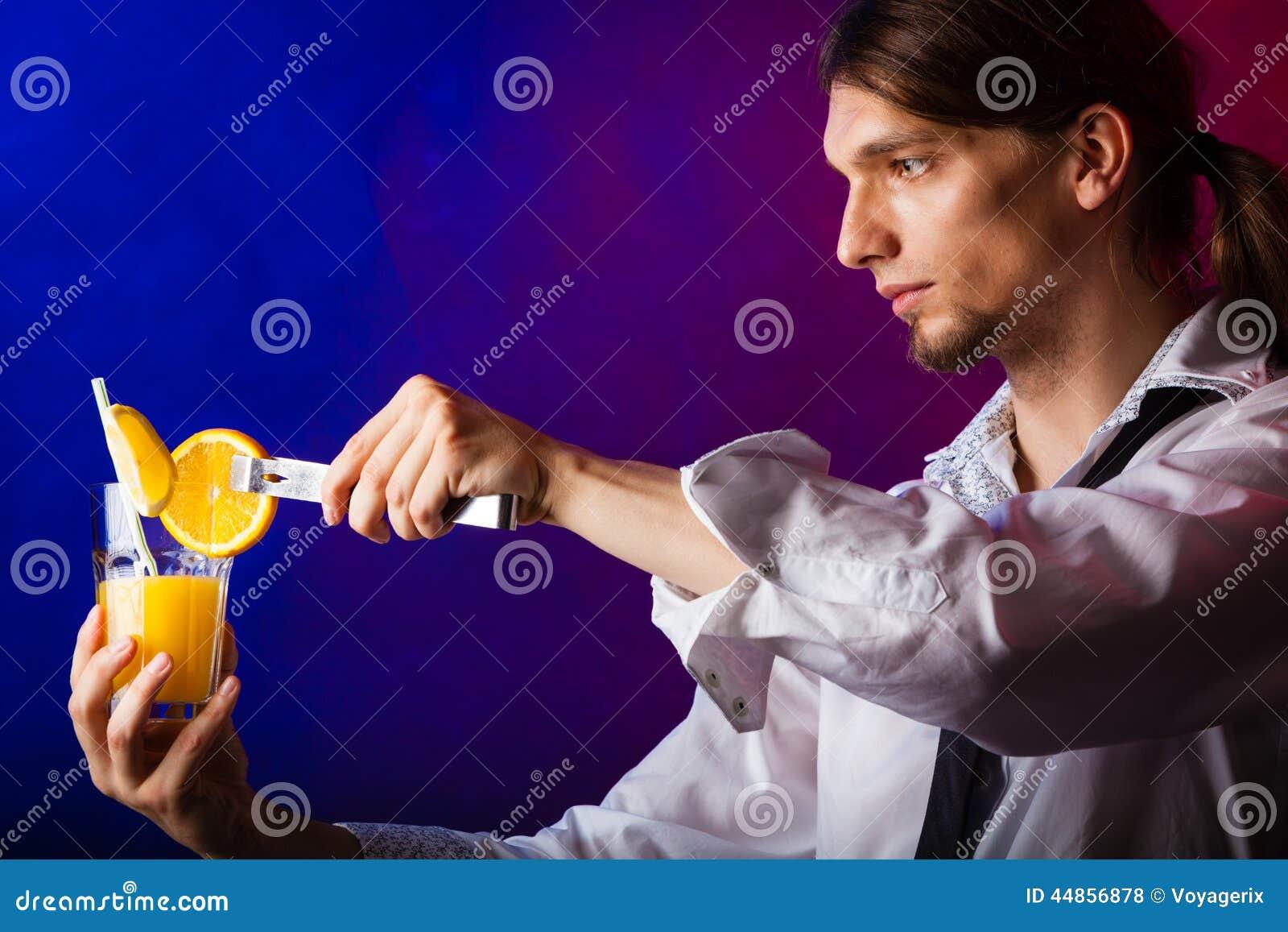 Camarero del hombre joven que prepara la bebida del cóctel del alcohol