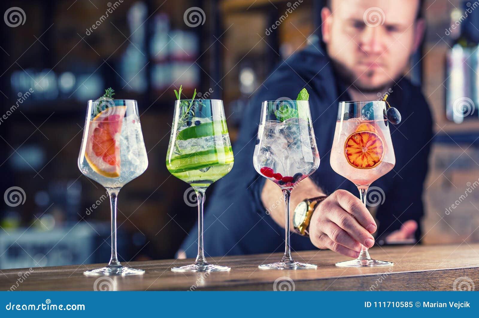 Camarero en el pub o el restaurante que prepara un drin tónico del cóctel de la ginebra