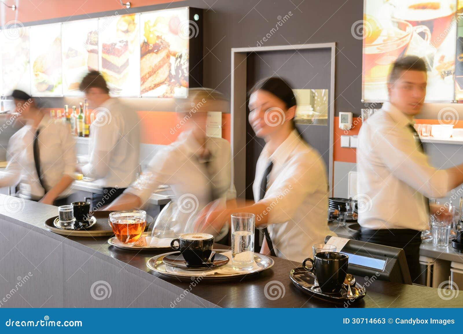Camarero ocupado y camareras que trabajan en la barra