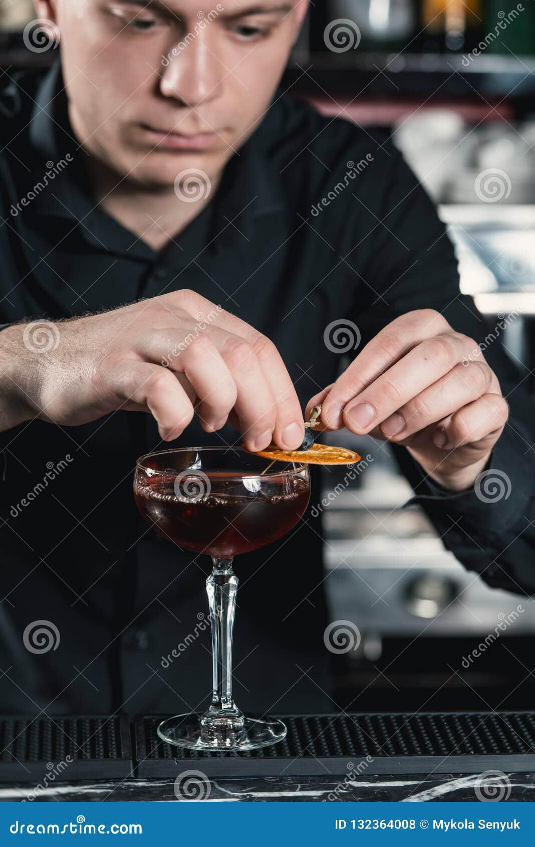 Camarero que hace el cóctel del acabamiento del cóctel de Boulevardier que pone la rebanada anaranjada en el top Barra en un fond