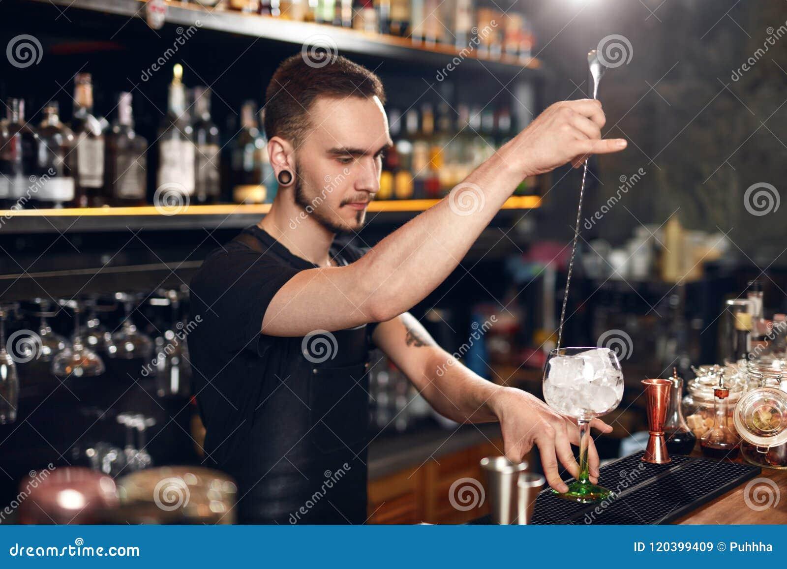 Camarero que hace el cóctel Vidrio de Putting Ice In del camarero