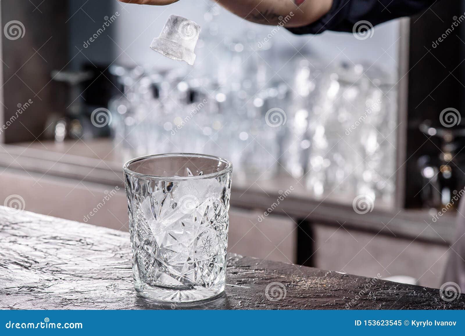 Camarero que hace el c?ctel Vidrio de Putting Ice In del camarero