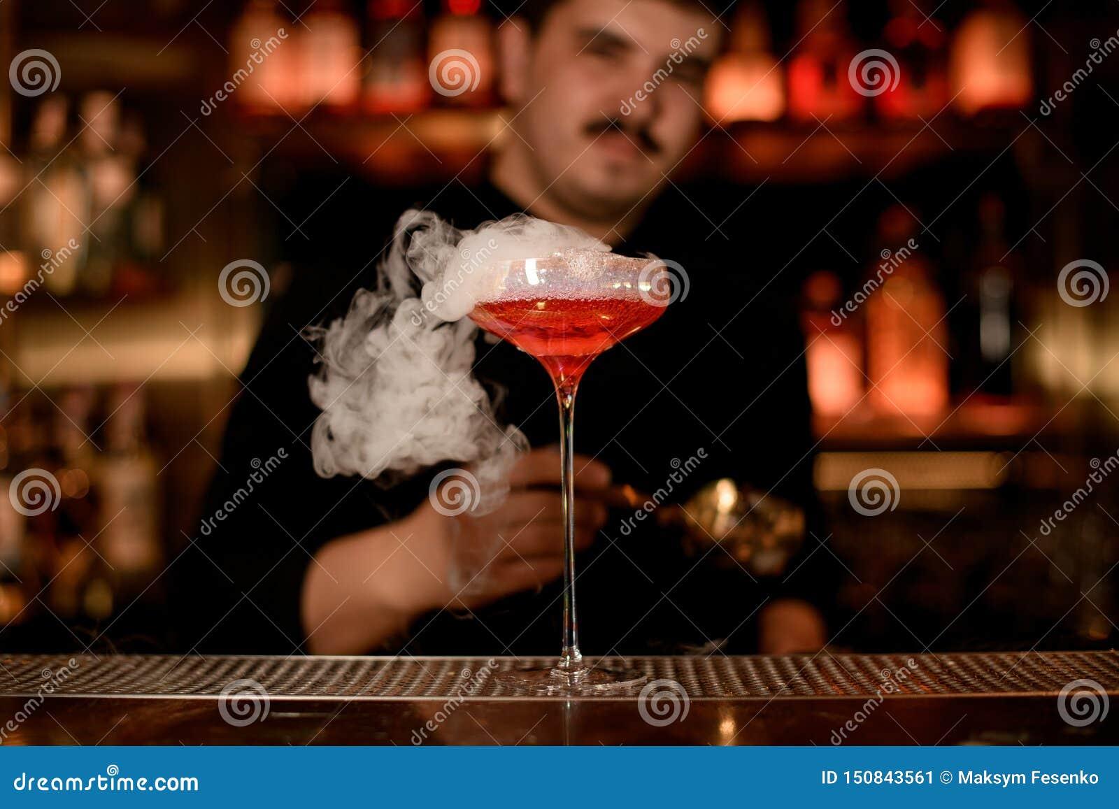Camarero que pone espuma en una bebida del alcohol