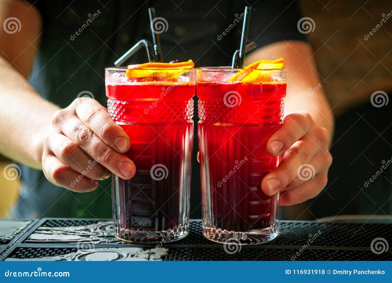 Camarero que sostiene dos cócteles en contador de la barra
