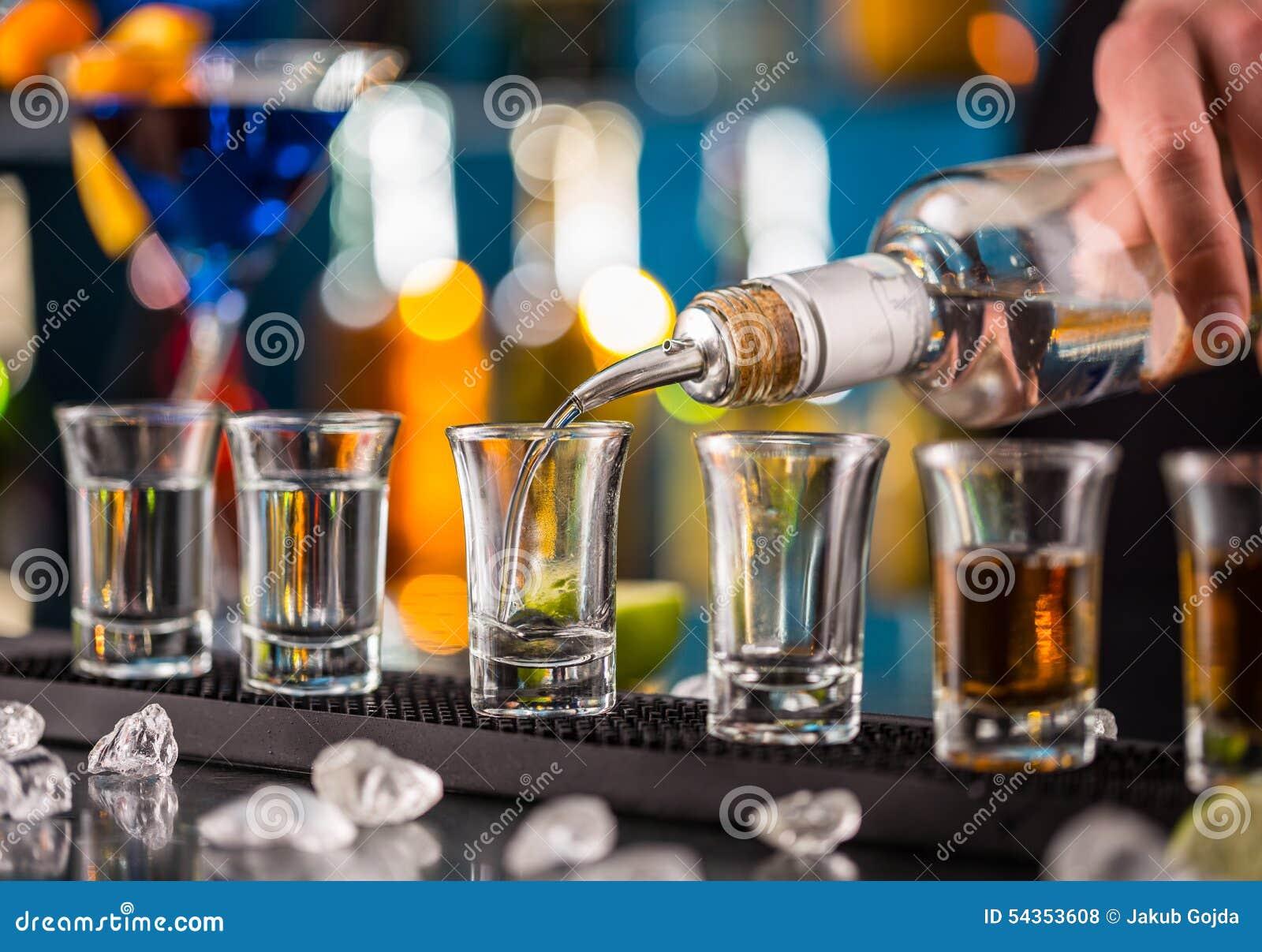 Camarero que vierte alcohol duro en los vidrios