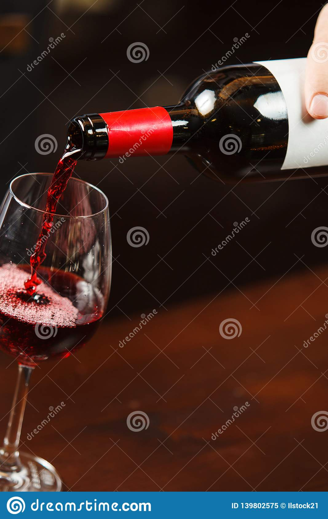 Camarero que vierte el vino rojo en la copa El Sommelier vierte la bebida alcohólica