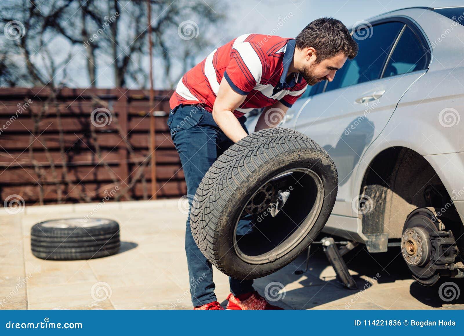 Cambio de un neumático de coche plano en el patio trasero Canse el mantenimiento, el neumático dañado del coche o los neumáticos