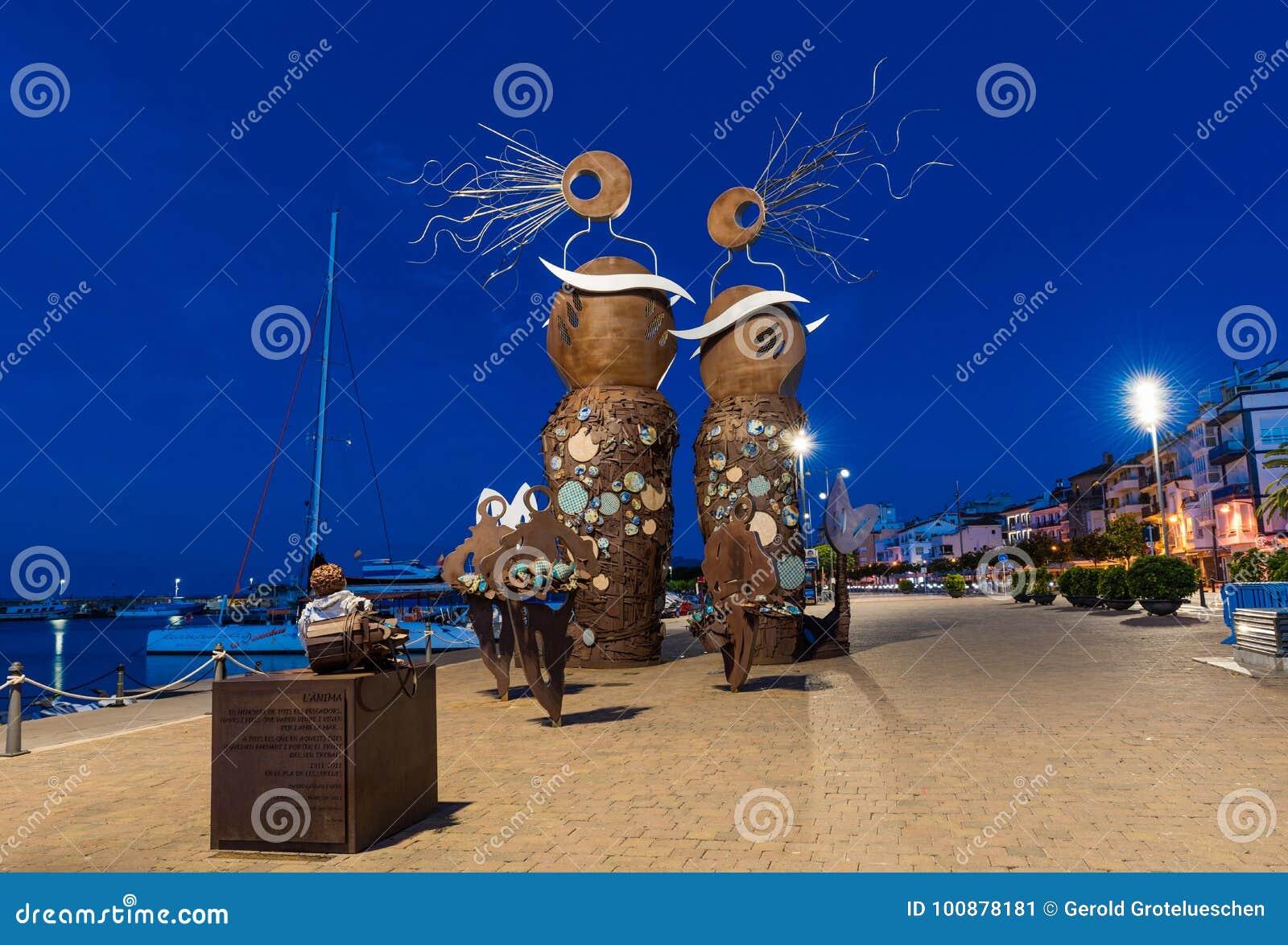 CAMBRILS SPANIEN - SEPTEMBER 16, 2017: Sikt av invallningen av staden och den moderna skulptur`en sjöjungfru`en,