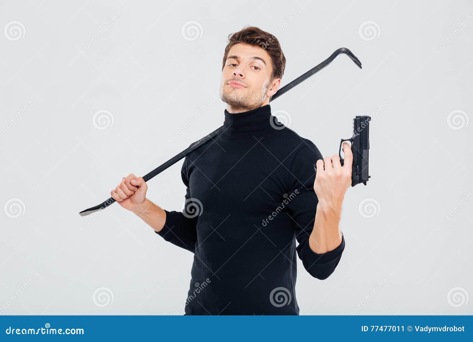Cambrioleur sûr de jeune homme posant avec l arme à feu et le pied-de-biche