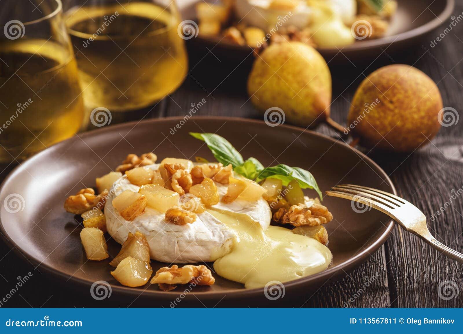 Camembert cocido con las peras y las nueces, servidas con el vino blanco