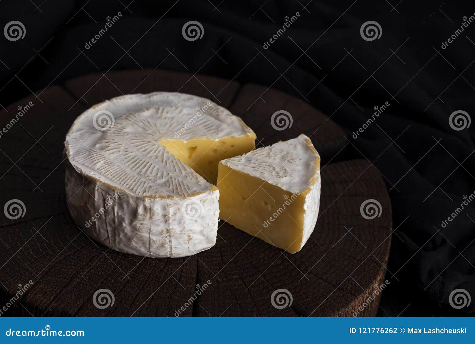 Camembert ser na czarnym drewnianym tle z kopii przestrzenią, głębokość pola płytki