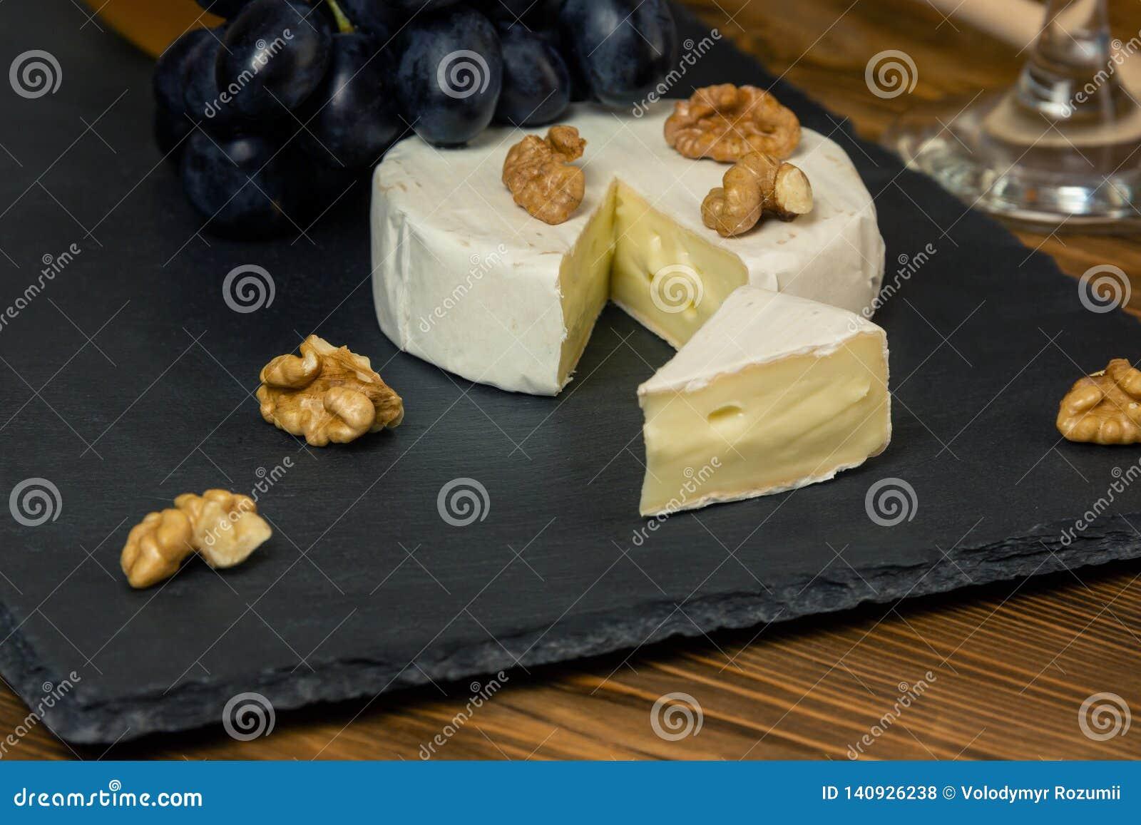 Camembertost i ett mörkt magasin bredvid söta blåa druvamuttrar och honung