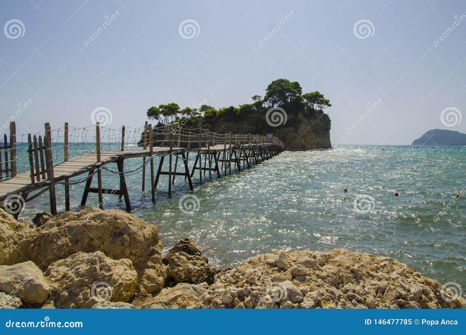 Cameo Island pequena e a ponte de madeira a Agios Sostis