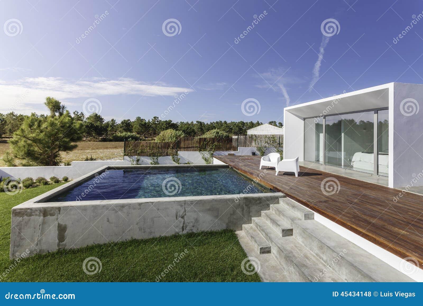Camera con la piscina del giardino e la piattaforma di for A forma di piani di casa con piscina
